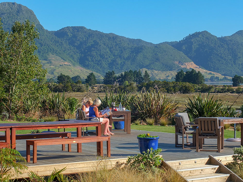 Relaxing while overlooking estuary with mountain backdrop