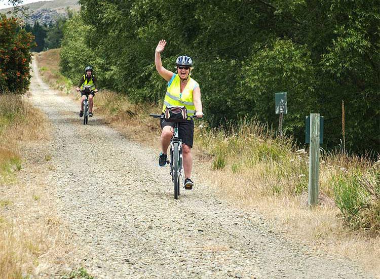 Happy cyclist waving while riding along the Otago Rail Trail
