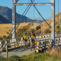 Cyclists riding across old Truss Bridge in River Valley