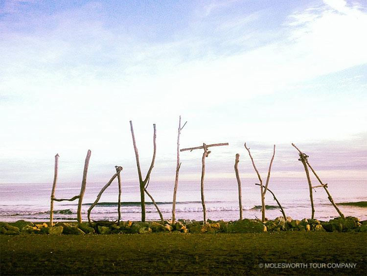 Hokitika sign built using driftwood on foreshore at sunrise