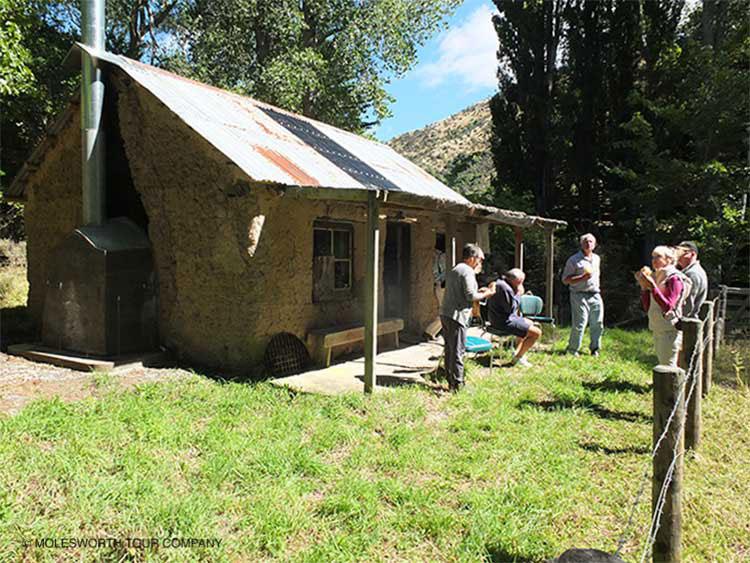 Tour group visiting historic cob hut
