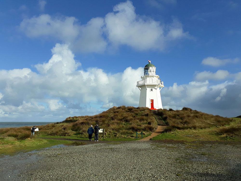 Tour group visiting Waipapa Point lighthouse on Catlins coastline